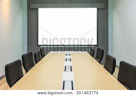 Blank projection screen in meeting room with conference table Modern meeting room interior background