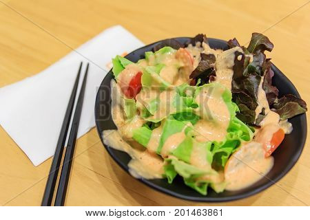 Fresh healthy salad and chopsticks on wooden table. View from above with copy space