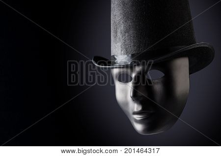 Black mask face closeup wearing black top hat on black background with copy space. Social masking and mystery concept