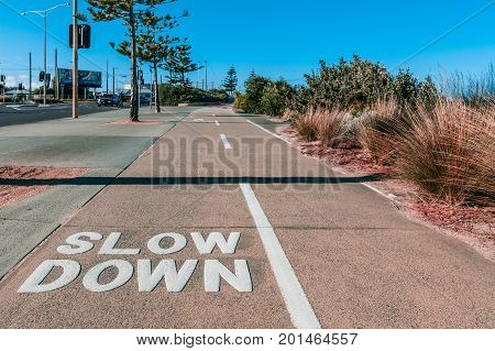Slow Down sign written on shared footpath for cyclists and pedestrians