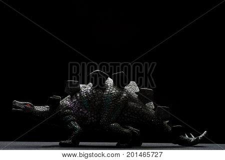 side view black stegosaurus toy on a dark background