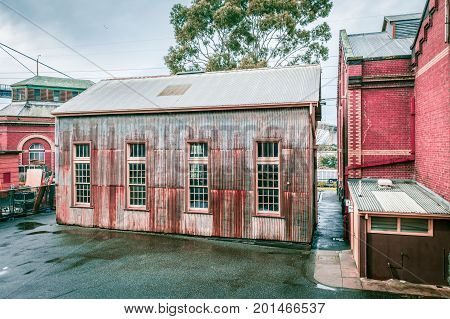 Old rusty metal shed with tall windows