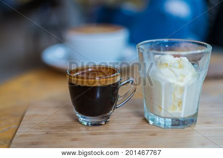 Affogato coffee or espresso with icecream on wood texture and blurred background