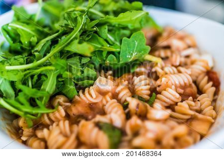 Closeup Of Brown Rice Fusilli Pasta Bowl In Marinara Sauce With Arugula Greens