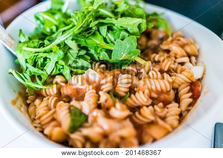 Closeup Of Brown Rice Fusilli Pasta Bowl In Marinara Sauce With Arugula Greens