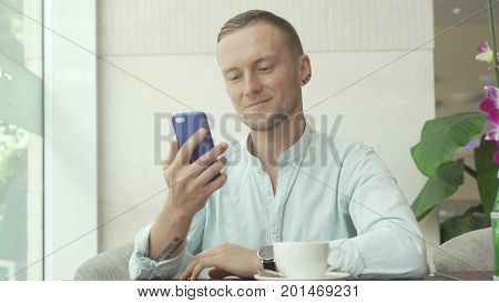 Young man answering message on mobile phone and drinking coffee