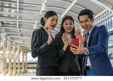 Asian business man and business woman doing conference call with someone on mobile phone