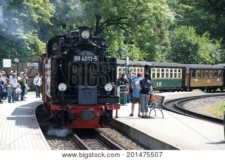 Binz, Germany - July 2, 2013: 'Rasender Roland', a steam locomotive train on germany island Rügen, in July 2013, with people getting on and off the train