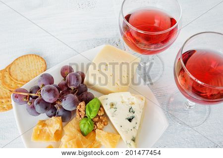 Two glasses of red wine different varieties of cheese walnuts red grapes and basil leaves top view