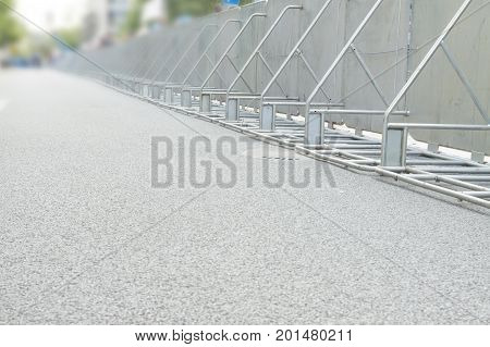 Metal crowd control barriers on the street sunlit