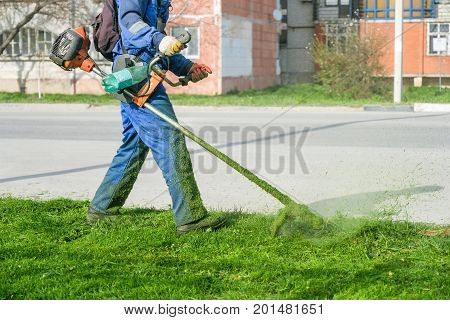 Man wearing overalls and rubber boots mowing green grass with gasoline lawn trimmer
