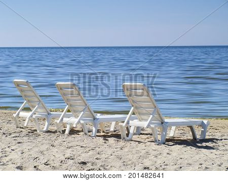 Three sun loungers on a deserted beach. The perfect concept of relaxation