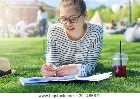 Closeup Photo Of Young European Lady Lying On Green Grass On Summer Day With Notebook Open In Front,