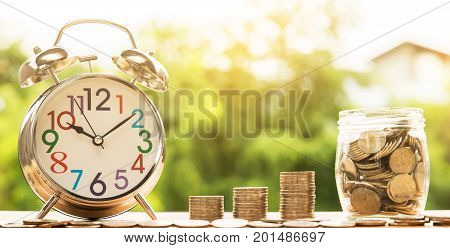 wooden house model and step of coins stacks and clock alarm nature background money saving and investment or family planning concept over sun flare silhouette tone.