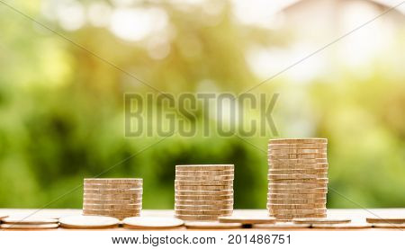 step of coins stacks with nature background money saving and investment or family planning concept over sun flare silhouette tone.