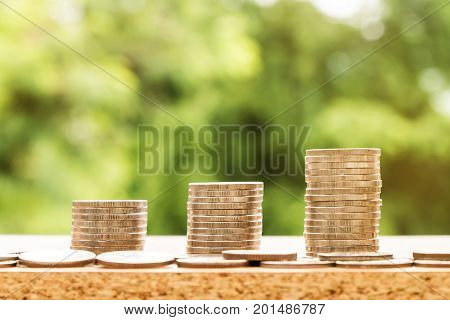 tep of coins stacks with nature background money saving and investment or family planning concept over sun flare silhouette tone.