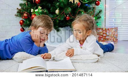 Two happy siblings at xmas eve. Childes brother and sister lying on the floor and reading book with christmas tree on the background.