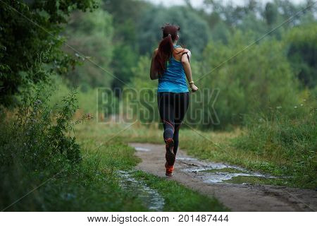 Photo from back of running girl in woods by day