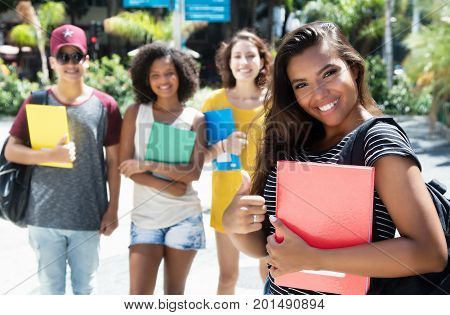 Beautiful latin american female student showing thumb with group of international students outdoor in the city in the summer
