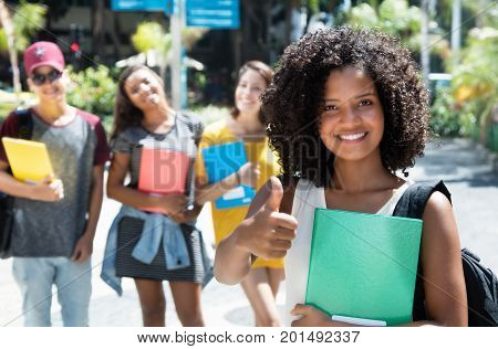 Laughing african american female student showing thumb with group of international students outdoor in the city in the summer