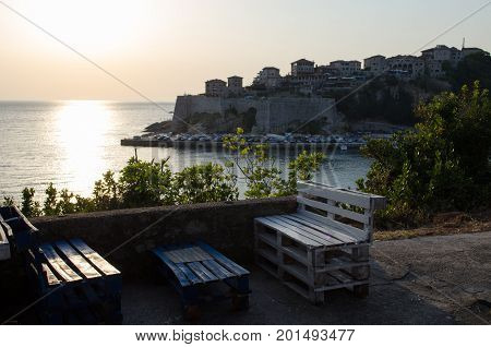 Cozy bar with the beautiful sunset view on sea and Stadi Grad - old town of Ulcinj at twilight scene. Coast of Adriatic sea. Montenegro.