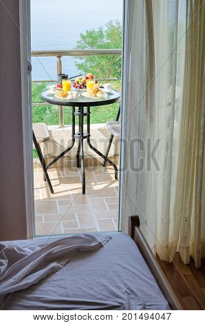Hotel room with fresh delicious breakfast with pastry coffee orange juice and fruits served on the balcony with sea view in the green location. Place for romantic holiday or honeymoon.