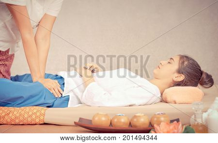 Women is getting thai massage on asian spa bed mat
