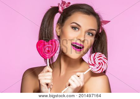 beautiful young woman with pink makeup and girly ponytails holding two sweet  lollypop. beauty shot on pink background. copy space.
