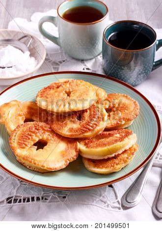 Apple fritters on blue plate and cups of tea