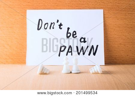 Pawns bow before the king and queen against the motivating inscription in English do not be a pawn