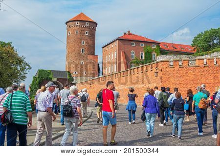 Krakow/Poland- August 14, 2017: Wawel Royal Castle, group of tourists walking to the palace complex main gate, passing by defencive fortification wall and Senator Tower