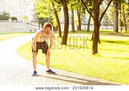 Pause in running. Redhead young adult man tired after running. Outdoor