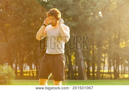 Young adult bearded sportsman listen a music in headphone. Outdoor shot