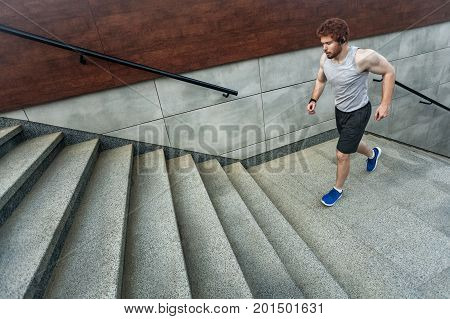 Running up on the stairs. Redhead athlete jogging on the stairs and left park. Outdoor