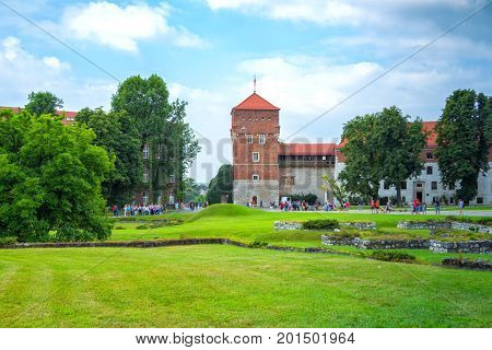 Krakow/Poland- August 14, 2017: Wawel Royal Castle, view of Thieves Tower,  tourists walking around the meadows and lawns of palace complex on a sunny summer day