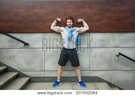 Poses as mister olympya. Show bicep. Smiling and looking at camera