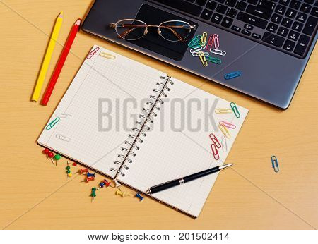 Office desktop with laptop opened notebook and pencils