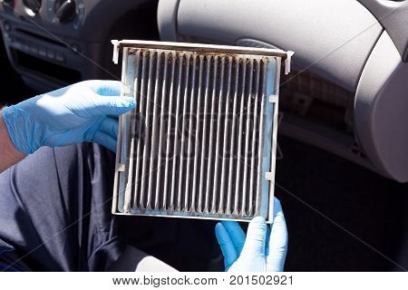 Dirty cabin air filter for the car. Replacing the old pollen air filter.