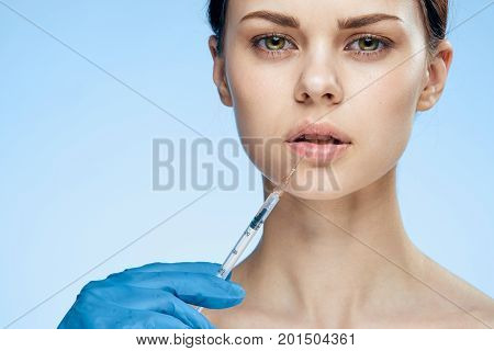 Beautiful young woman on a blue background holds a syringe, plastic, medicine.