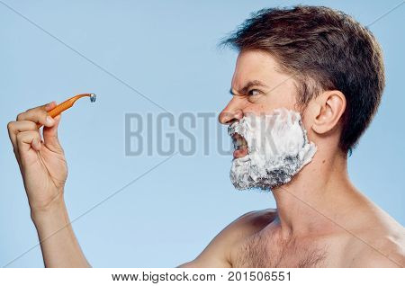 Young guy with a beard on a blue background shaves.