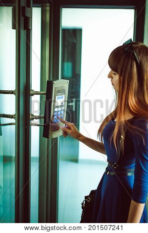 Attractive Woman In A Blue Elegant Dress, Dials Code Into Intercom, At Entrance Of House