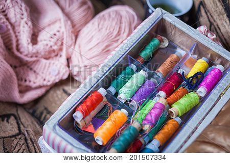 The still life of a tangle of pink woolen threads an unbound pink sweater and a multitude of coils of thread of different colors in the box in even rows lie on a brown vein the top view