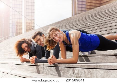 Group of multiethnic athletes doing elbow plank exercises, standing in a line outdoors on city stairs
