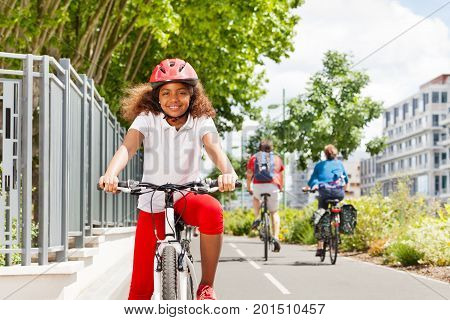 Portrait of happy preteen African girl in safety helmet cycling on bicycle path in summer city