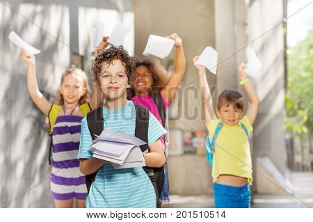 Nice handsome young boy with paper near the school and group of friends on background