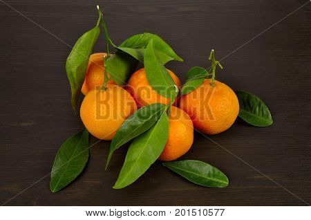 Mandarine orange with green leaves on dark wood background