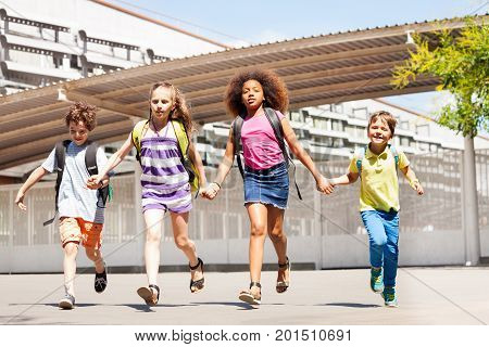 Boys and girls run in front of the school yard happy holding hands smiling