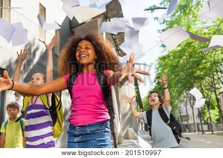 African girl among group of happy kids throwing papers in the air near the public school with big smile and spread hands