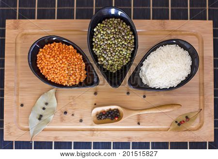 White Rice, Red Lentils And Green Peas Mache In A Black Glass Plate On Wooden Table. Bay Leaves And