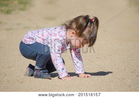 Little Girl Playing On The Ground With The Sand